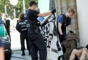 A German police officer looks at a banner belonging to members of far right Identitarian movement  after the activists staged a demonstration on top of Brandenburg Gate in Berlin