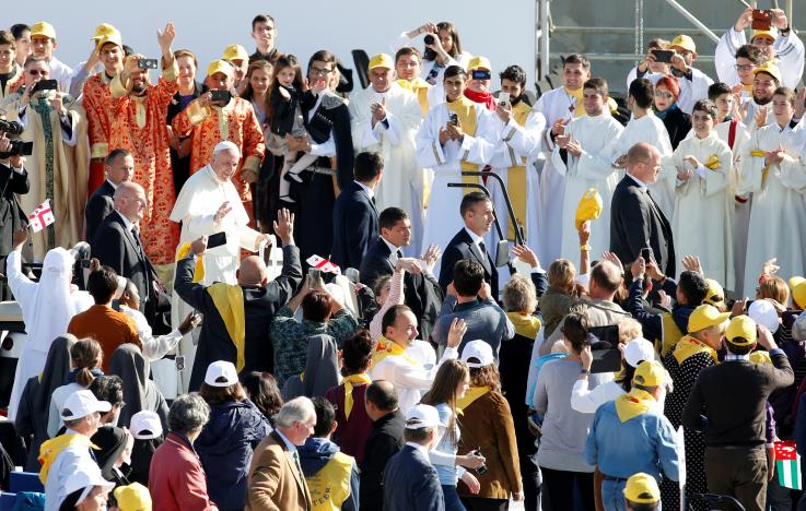 Pope Francis waves as he arrives for holy mass at Mikheil Meskhi stadium in Tbilisi