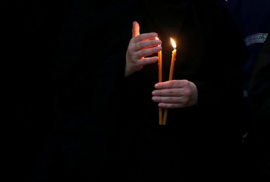 A nun holds lit candles during a Good Friday religion service at Holy Trinity cathedral in Tbilisi