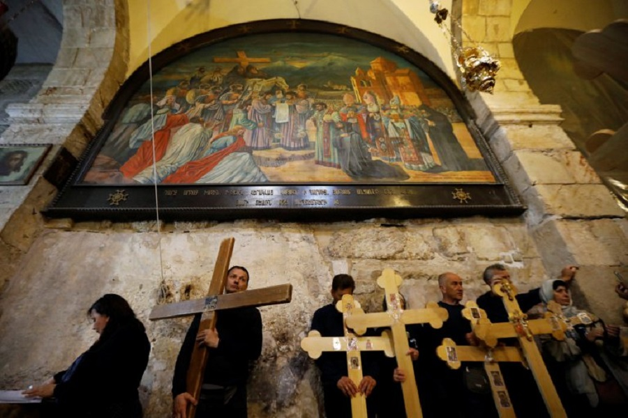 Worshippers carry crosses inside the Church of Holy Sepulchre during a Good Friday procession in Jerusalem's Old City